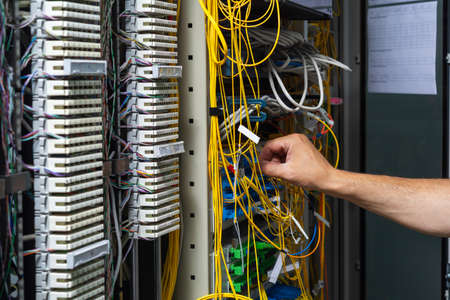 Hands of a technician crossing a telecommunication panel cable in a rack