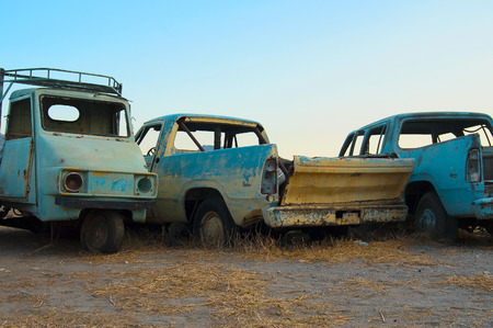 motorcar: Motorcar and two rusty old American cars in light blue background sky in a desert place