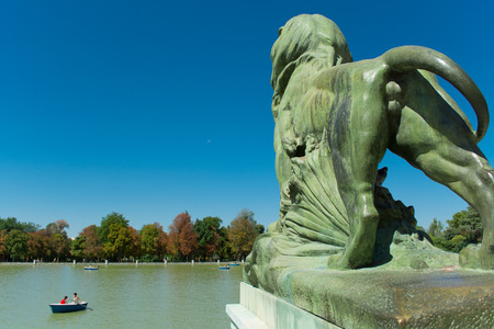 crowd tail: Bronze Lion back side, Monument of Alfonso XII, Pond of the Park of the Pleasant Retreat, Madrid, Spain