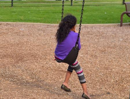 friendless: sad girl sitting on the swing on the playground
