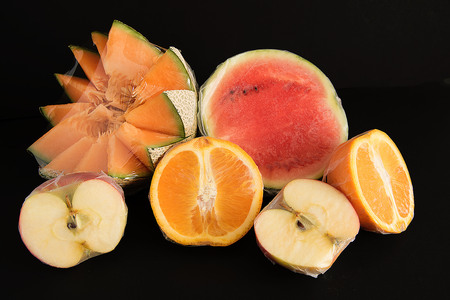 Various fruits packed in plastic film on black background Stock Photo