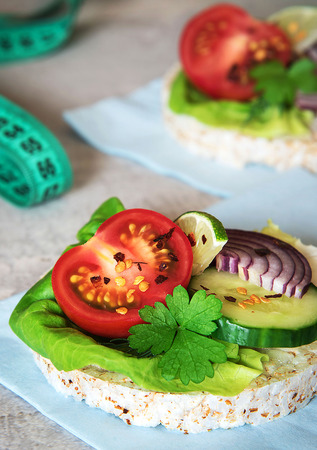 Healthy food - sandwiches, rice cakes with lettuce, tomato, cucumber, onion and parsley. With tape measure, centimeter