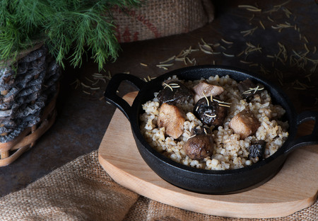 Barley porridge with forest mushrooms and meat in cast iron. Stock Photo