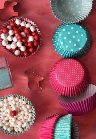 Bake tools for cookie and colorful cupcake baking cupon pink background. top view