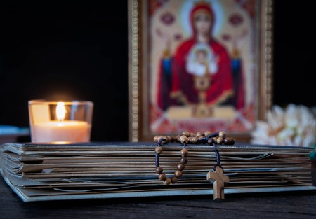The time for prayer. Wooden Rosary on an ancient prayer book. Icon of the Mother of God and Jesus. Lighted candle.
