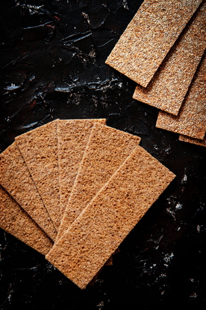 Crispy rye crackers on black board background.