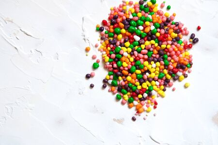 Rainbow colored candy sprinkled on a white background.