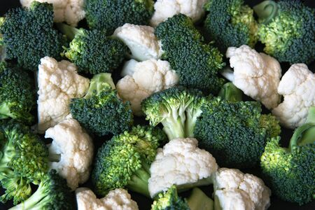 Pieces of ripe broccoli and cauliflower. Healthy background. Stockfoto