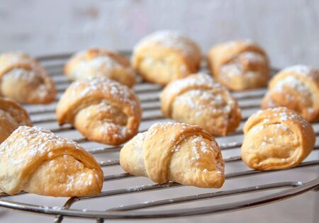 Homemade mini croissants on a on the grid. Confectionery menu concept. Stock Photo