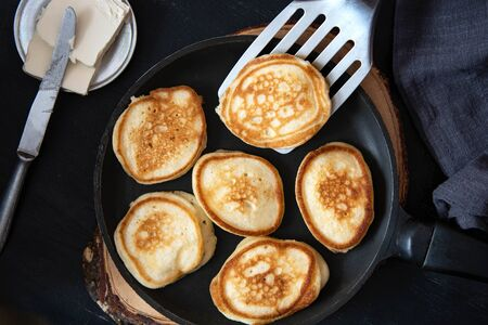 Small pancakes in a pan on a wooden board.