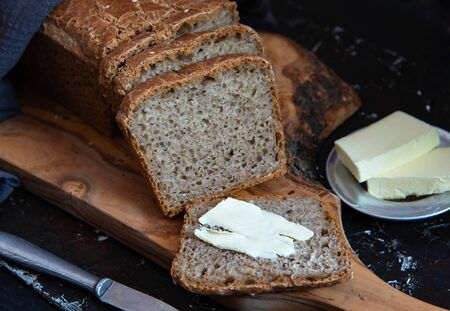 Homemade whole grain bread with with seeds. A piece of bread with butter.