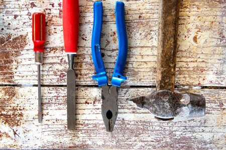 Retro woodwork equipment set. Hammer, screwdriver, chisel, pliers on texture wooden planks background. Top view.