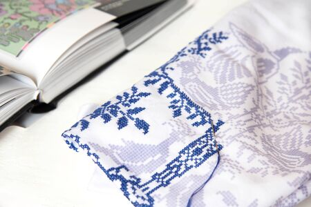 A close up of a cross stitch embroidery. Cross-stitch ornament and book with embroidered ornaments. Banco de Imagens