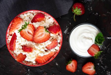 Cottage cheese with strawberries and sour cream on a black background. Healthy dessert. Stok Fotoğraf