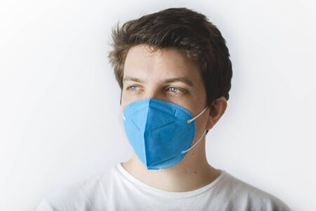 EUROPEAN CAUCASIAN YOUNG MAN IN WHITE BACKGROUND WEARING A FFP2 BLUE FACE MASK PREVENTION DURING QUARANTINE TO AVOID THE SPREADING OF COVID-19 CORONAVIRUS