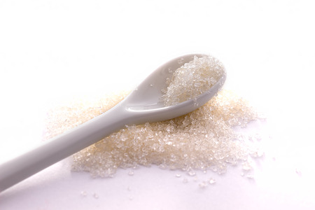 White spoon of sugar on a white background