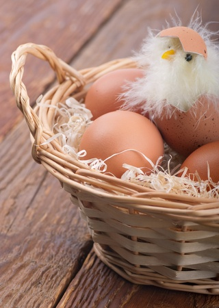 hatched: Hatched chicken in a basket with eggs on the table Stock Photo