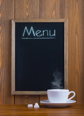 White cup and chalk board with the menu photo