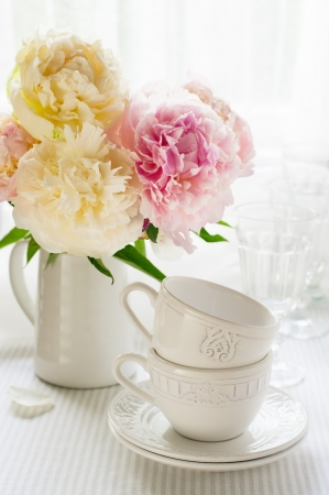 dinnerware: White cups and a bouquet of peonies on the table