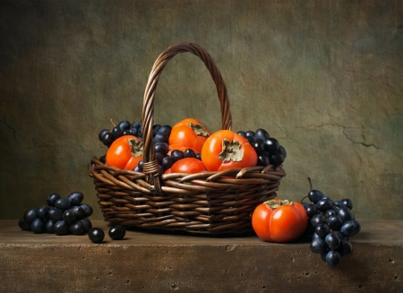 Still life with persimmons and grapes in a basket photo