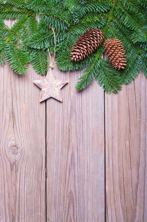 Fir branches with cones and star on wooden boards photo
