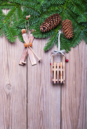 Fir branches with cones  and  Christmas decorations on wooden boards photo