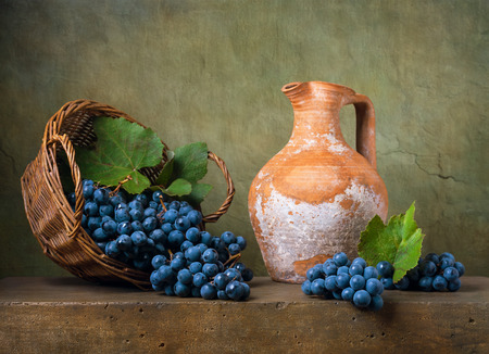 Still life with grapes on a basket and jug