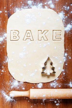 holiday meal: Dough with letters and rolling pin on the wooden table. Kitchen background