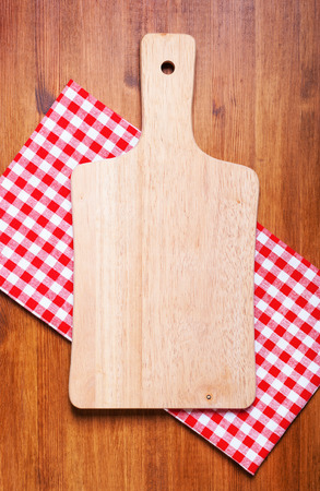 Kitchen cutting board and a towel on the wooden table