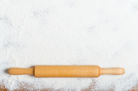 plunger: Sifted flour and rolling pin on the table. Kitchen background