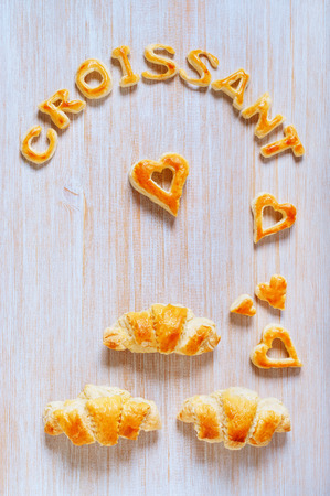 savour: Croissants and letters of dough on the wooden table