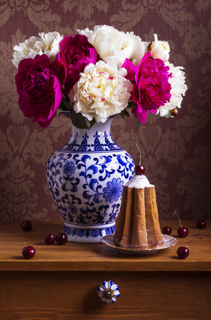 Still life with peonies in a chinese vase and cake