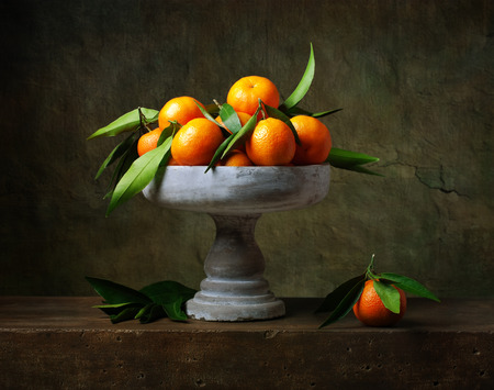 Vintage still life with tangerines in vase for fruits Stock Photo