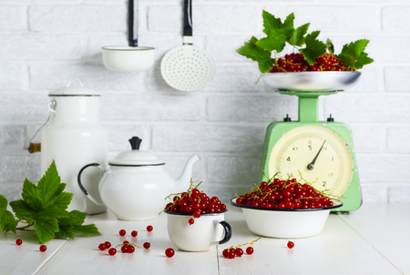 Red currant berries in a cup and bowl on the kitchen table Reklamní fotografie