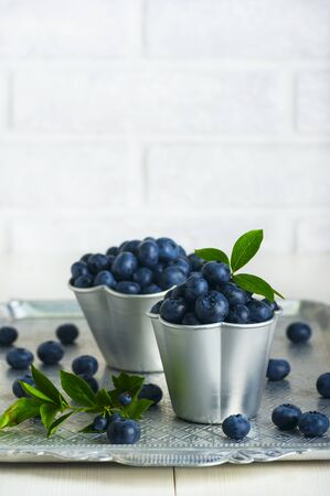 Blueberries with leaves in aluminum cups Banco de Imagens