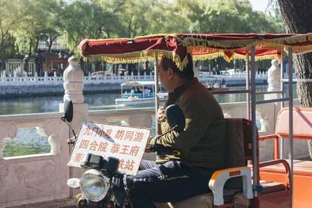 25,Oct,2014 -Beijing,China. side profile of Man on rickshaws at Houhai Lake. Tourists can have  a rickshaw tour around Houhai Lake to explore the ancient hutongs and traditional building. the board show  the name of places he can go Editoriali