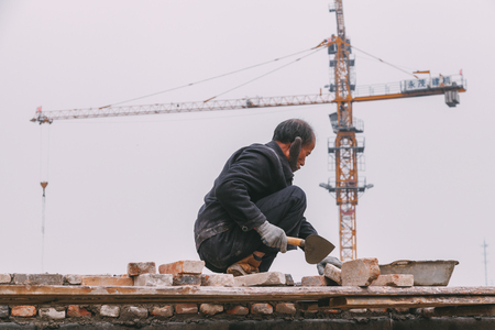 18 Dec,2014 Beijing. a men on a construction site in City with cranes ,takeing Bricks andbuilding train station