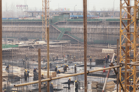 18 Dec,2014 Beijing. Work activity on a construction site in City with cranes and workers,building train station 報道画像