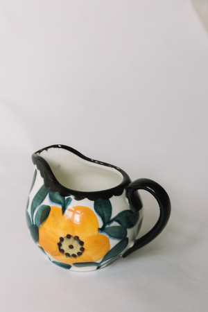 a white tea cup  with floral and line pattern on white background