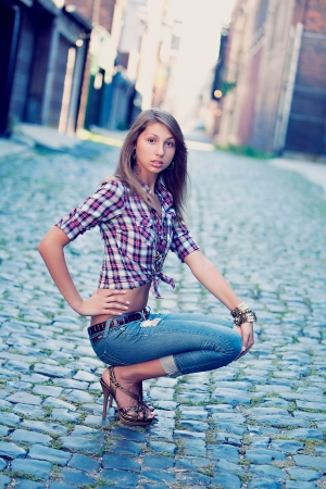 A young girl poses on a cobble stone street wearing high heels photo