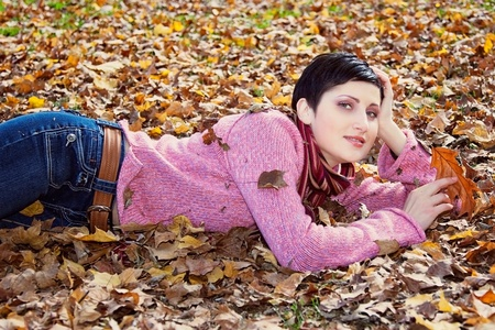A beautiful woman laying on the ground surrounded by autumn leaves