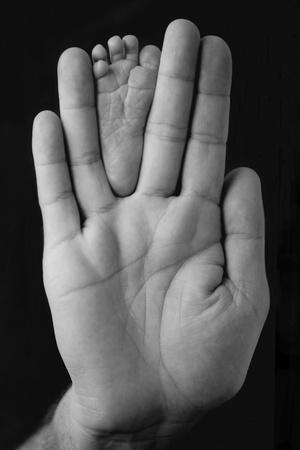 pies bonitos: Pies del beb� reci�n nacido envueltos en la mano del padre