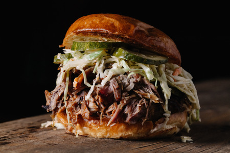 BBQ Pulled Pork Sandwich with bleu cheese slaw and dill pickles on horisontal dark background Stock Photo