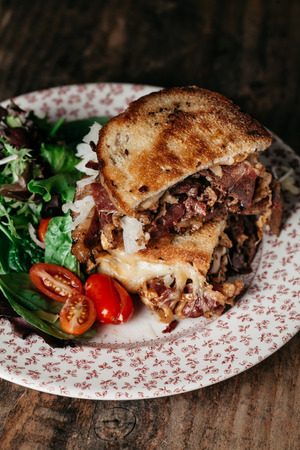 Reuben sandwich on toasted rye bread, made with pastrami meat, Swiss cheese, sauerkraut and dressed with thousand island dressing Stock Photo