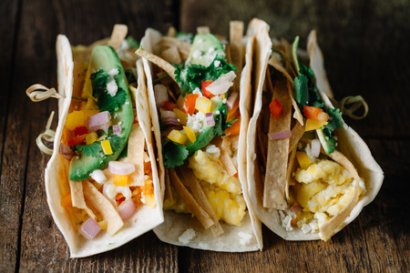 Breakfast tacos with scrambled eggs, avocado, fresh pepers and onions on rustic surface Stok Fotoğraf