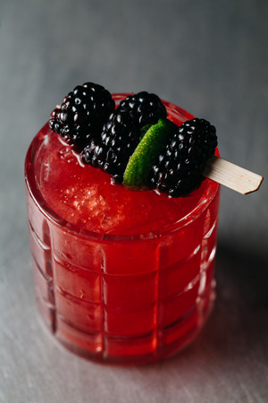 Alcoholic drink garnished with blackberries and lime in muted silver background Stock Photo