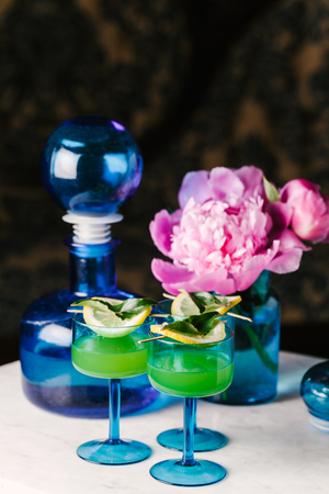 Beautifully styled tequila cocktails in vintage blue glassware on a marble table