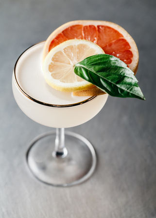 Alcoholic drink in a martini glass garnished with blood orange and basil on silver background Stock Photo