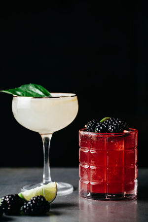Two alcoholic drinks garnished with fruit and berries on dark background Stock Photo