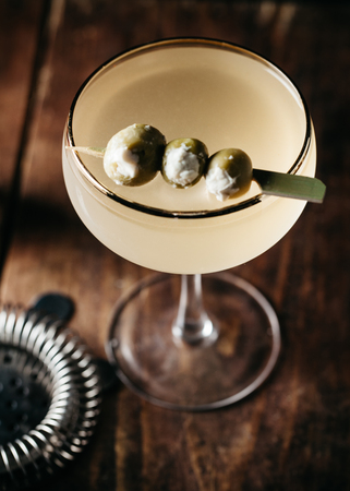 A martini garnished with stuffed olives on wooden surface, vertical